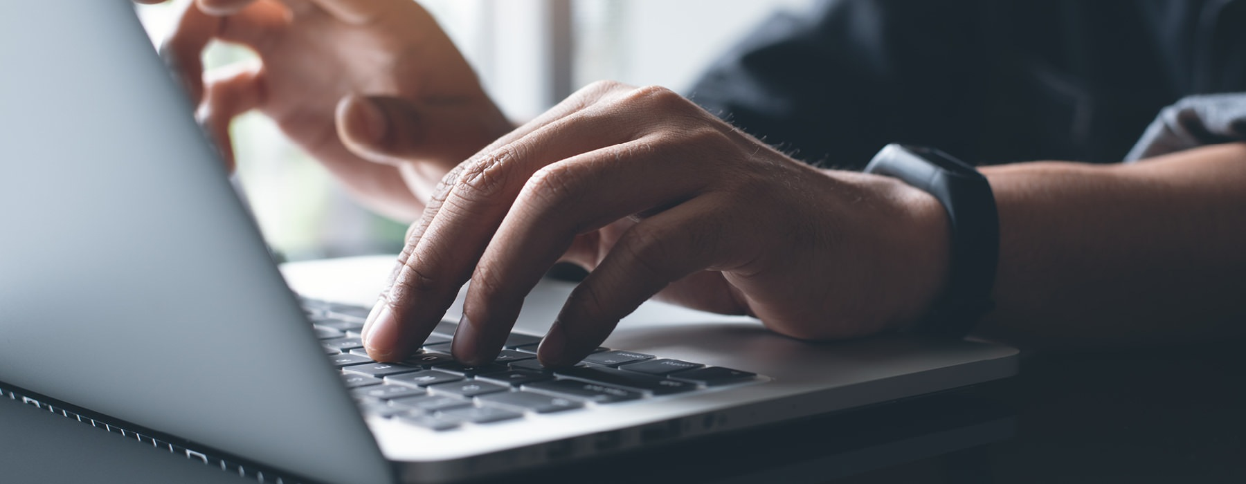 man sitting at a table typing on a laptop