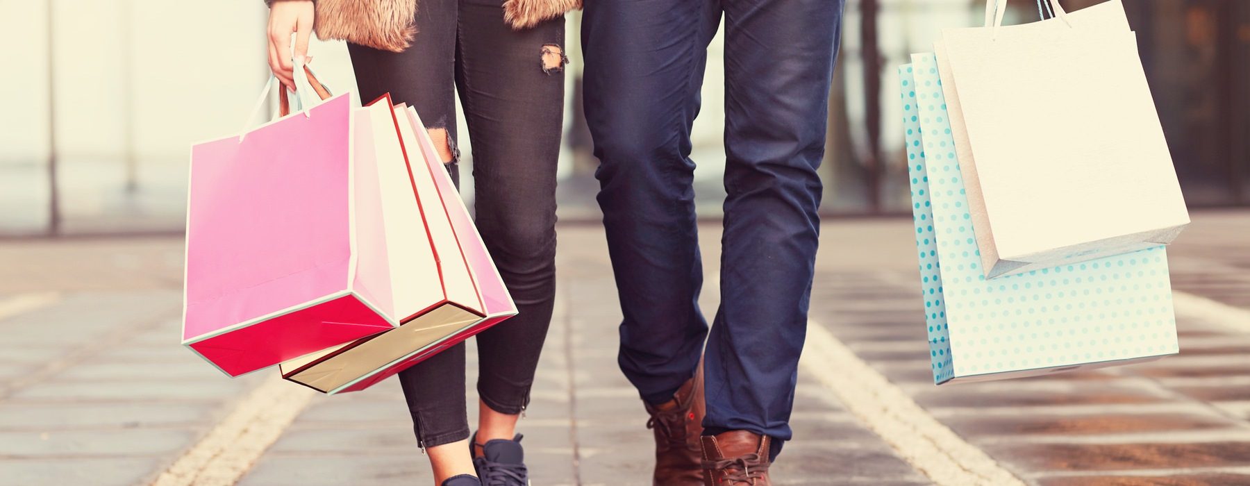 man and woman walking down the street holding shopping bags